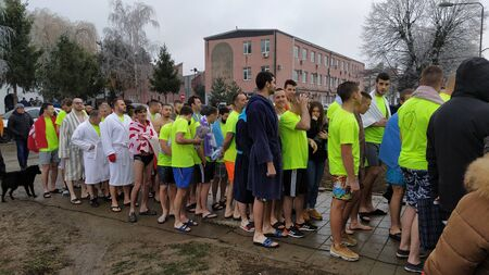 Sremska Mitrovica, Serbia - January 19, 2020 Religious bathing on the river on the day of the Epiphany. Christian holiday. Young athletes are preparing for a swim in cold river water. Bright T-shirts