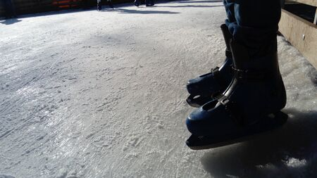 Feet with skates. Sports uniforms and equipment. Ice rink. Long shadows on ice from the low winter sun