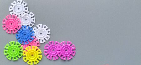 Multicolored details in the form of snowflakes from the childrens designer on a gray background.Red, yellow, green, blue, white, pink plastic discs for the development of fine motor skills of fingers