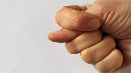 A fist with a thumb stuck between the index and middle. A rude gesture indicating mockery, contempt, and a desire to humiliate an opponent. Failure in a rude manner Banco de Imagens