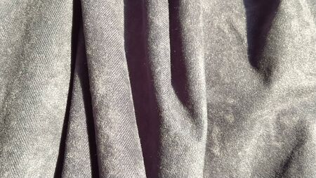 Close-up of velvet thick fabric for curtains. Blue-gray color. The material hangs in waves. Sample for home decoration. Corduroy piece of fabric