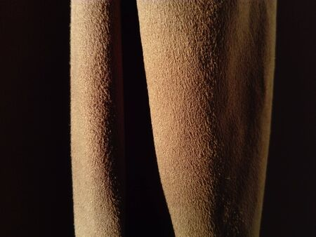 Brown velvet fabric. Dense, pleasant to the touch curtains close-up. Variant of interior decoration. Overflowing shades of brown on a short pile of material. Sewing product.