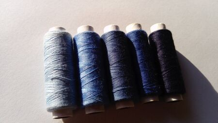 Close-up of several bobbins and spools of thread in different shades of blue. A white background.