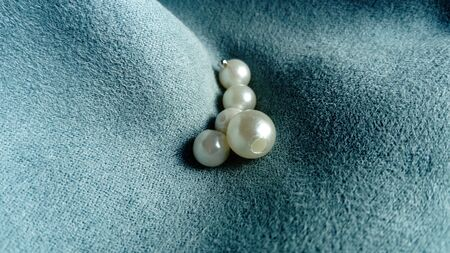 White beads lie on a velvet blue fabric. Jewelry on the curtains. A beautiful combination of mother-of-pearl shine and light tints on a short pile of velvet. Creases and waves on the fabric. 版權商用圖片