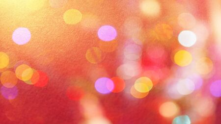 Festive warm background or greeting card. Sun glare on a bright red background. The nuances of orange, yellow, pink, lilac, beige and white. Bokeh effect.