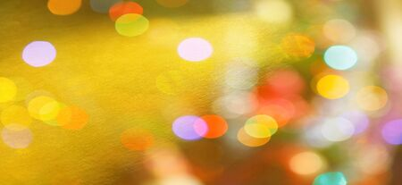 Festive warm background or greeting card. Sun glare on a bright yellow background. The nuances of orange, yellow, pink, lilac, beige and white. Beautiful bokeh effect.