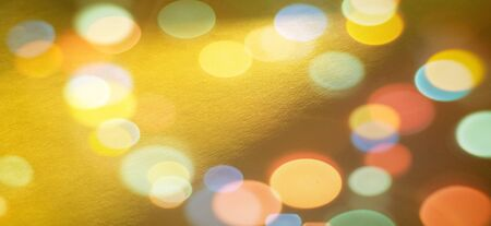 Festive warm background or greeting card. Sun glare on a bright yellow background. The nuances of orange, yellow, pink, lilac, beige and white. Beautiful bokeh effect