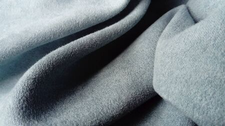 close-up of velvety thick fabric for curtains of gray-blue color pleated with the play of chiaroscuro.
