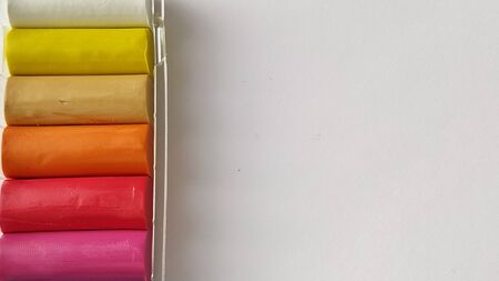 Multi-colored plasticine in plastic packaging on a white background.