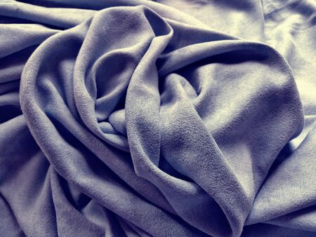 Fabric for curtains and curtains. Beautiful gray purple. Soft velvet with velvet. The curtain material is carelessly folded on a horizontal surface. Fabric sample. Interior Design Option