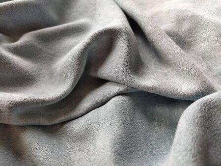 Fabric sheer curtain fabric. Beautiful gray-blue color. Soft velvet with a pile. The curtain material is carelessly folded and wrinkled on a horizontal surface. Fabric sample. Interior design option.