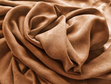 Fabric for curtains and curtains. Beautiful brown - terracotta color. Soft velvet with velvet. The curtain material is carelessly folded on a horizontal surface. Fabric sample. Interior Design Option. 写真素材