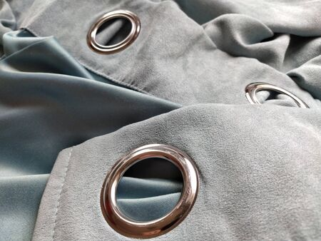 two metal eyelets on gray-blue velvet curtains.