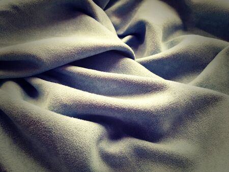 Cloth Curtain. Beautiful gray-blue color. Soft velvet with velvet. Curtain material folds casually on a horizontal surface. Sample fabric for the interior.Dark vignetting around the edges of the image