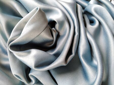 Silky to the touch fabric of gray - blue color with a brilliant shimmer. Natural lighting, light and shadow. The material is casually folded. Polyester Textile