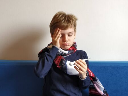 The boy got sick, his head hurts. Viral disease is progressing. The childs neck is wrapped in a warm scarf. The kid looks dejectedly at the thermometer, holds his hand on his forehead and suffers. Archivio Fotografico