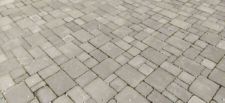Cobbled street of the old city, lined with square and rectangular stone tiles in a chaotic manner. Soft gray color. The texture of the stone. Geometric pattern Stockfoto