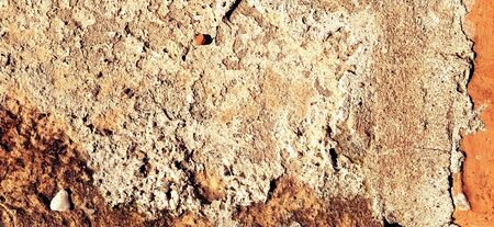 Brick or stone close-up. Texture or background. Bright red, brown, orange, beige colors. Dust, small pebbles, sand, soil and moss on uneven surfaces.Environmental impact. Natural daylight or sunshine. 免版税图像