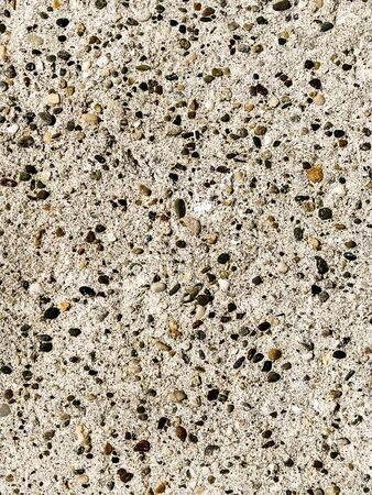 Concrete surface with multi-colored blotches of small stones. Light beige tone. Wall of a building or concrete slab. Close-up. Pockmarked cement surface. Interior or exterior finish option.