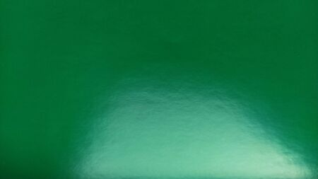 Green sheet of shiny colored paper. The reflective surface glares in the light. Bright intense color. Beautiful background. Highlight from below. Green turning into blue. gradient.