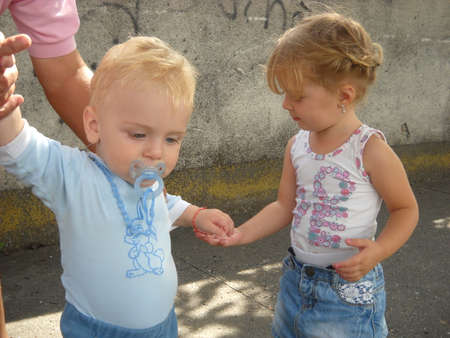 Sremska Mitrovica, Serbia - July 01, 2019 Children walk accompanied by adults. A boy and a girl met on the road. Kids get to know and communicate. The baby has a blue nipple in his mouth.