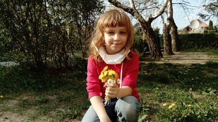 A pretty girl of 6 years old with blond hair crouched on the lawn and holds in her hand a bouquet of yellow wildflowers. White protective surgical mask lowered from the face. Allergens and viruses. Foto de archivo