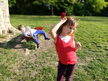 The boy is in love with a girl. First unhappy love. Partially defocused photo. The boy falls off the bench with the impression of a girls beauty or disappointment. Emotions and gestures. Girl puts a red flower on her hair