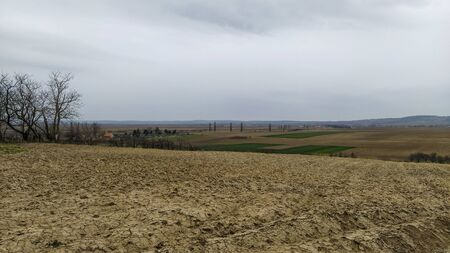 Freshly plowed field. Arable land with fertile soil for planting wheat. Rural landscape in Serbia, Balkans, namely Fruska Gora from Sremska Mitrovica. Furrows and pits. Preparatory agricultural work.
