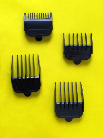 Nozzles for hair clippers. Four black plastic combs - a limiter for measuring the length of the cut hair. Nozzles from 1 cm to 4 cm. Hairdresser tools on a yellow background. Hair Salon Equipment.