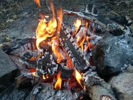 Burning firewood in a fire. Bright fire. Tongues of flame of orange color. Big stones - boulders around a campfire.