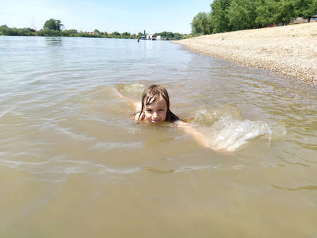 Sremska Mitrovica, Serbia - May 10, 2020. A girl is swimming, looking at the camera and laughing. Sava River. Turbid water in the pond. Happy child 6 years on vacation. Sandy beach and the horizon in the background