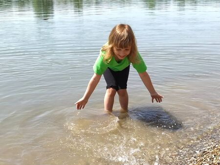 Adorable curly baby girl splashing in a beautiful river on a sunny summer day. The child is dressed in a green T-shirt and black shorts.