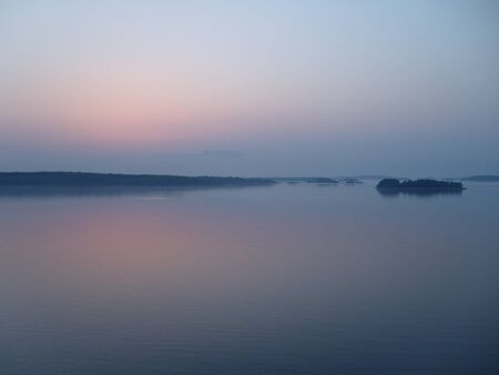 White nights on the Baltic Sea. Finnish skerries in fog and night haze. A beautiful landscape in taupe. Pink and blue colors of the sky and water. Skyline. Reflection of the sky in the water.
