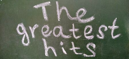The phrase The greatest hits is handwritten in white chalk on a dark green blackboard. Foto de archivo