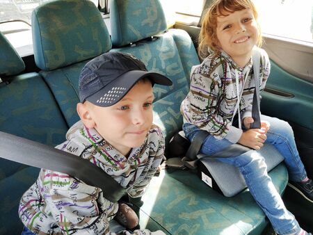 Children in the car. A boy and a girl are sitting in the back seat, laughing and grimacing. Children fasten their seat belts. A child in a cap. Twins of different faces dressed in the same clothes