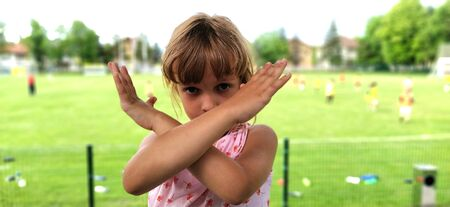 Beautiful girl with brown hair shows hand gestures. Crossing of hands, signifying the end, prohibition, no, stop. In the background is a soccer field. Game over.