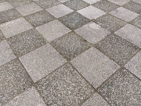 Chess tile. Monochrome asphalt markings on the sports field. Stone tiles with dark and light finish. Squares or rhombuses photographed diagonally. Rough rocky surface. Foto de archivo - 150128751