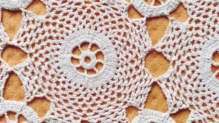 Hand crocheted white lace. Round napkin for table or chest of drawers. Ornament in a traditional rustic style. Neat crochet or knitting work. Cotton white threads. Orange background.