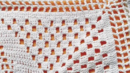 Hand crocheted white lace. Napkin with square and diamond-shaped holes. Ornament in a traditional rustic style. Neat crochet or knitting work. Cotton white threads. Orange background.