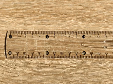 Transparent plastic school ruler on a wooden table. Millimeters and centimeters are marked in black. Measuring length and width with a ruler.