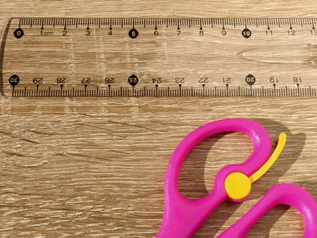 Transparent plastic school ruler on a wooden table. Millimeters and centimeters are marked in black. Measurement of length and width with a ruler. Bright pink scissors. Flat lay.