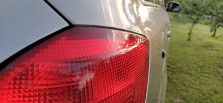 Detail of the rear end of a silver car with focus on the brake lights. Red rear light of the car. Brake signal for the driver driving behind.