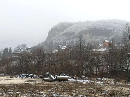 Beautiful winter european landscape with a mountain in the background. Snow falls in large white snowflakes. Winter calm in the countryside. In the foreground is a dirt site with construction debris Stok Fotoğraf