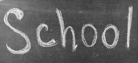 The inscription School on the school black chalkboard, handwritten in white chalk