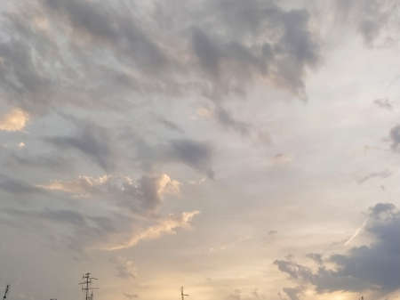 Beautiful dramatic sunset. The sky turned yellow. Dark gray clouds. Clouds lit by the lateral evening sun. Soft warm tones and colors. Summertime atmosphere.