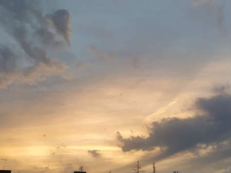 Beautiful dramatic sunset. The sky turned yellow. Dark gray clouds. Clouds lit by the lateral evening sun. Soft warm tones and colors. Summertime atmosphere Stock fotó
