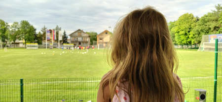 Sremska Mitrovica, Serbia, August 1, 2020. A girl sits with her back to the camera and watches a football match of childrens teams. Beautiful long blonde hair. Soccer fans in a match.