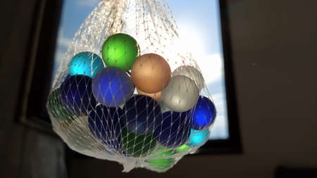 Multi-colored clickers or glass balls for decoration. Blue, green, beige balls are suspended in a net in the air against the window and the sky. The light of the sun shines through glass.