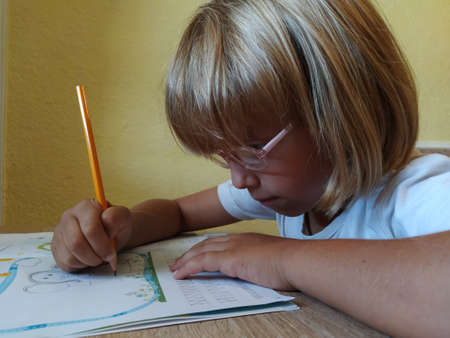 A 6 or 7 year old girl draws in a book. The child does his homework. Blond hair and pink-rimmed glasses. Training and education concept.