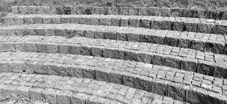 Semicircular steps of the amphitheater. Wide staircase made of stone blocks or bricks. Uneven bricks. The old steps are circular. Monochrome black and white photography